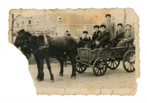 En route to county fair – Cuţa holding horse reins (c. 1960)